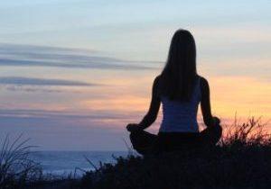 woman-meditating-sunset